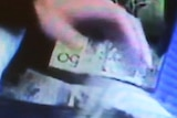 A still from CCTV footage shows a hand removing wads of $50 notes from a blue cooler bag.