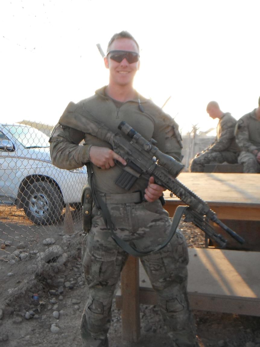 An Australian soldier holds a gun