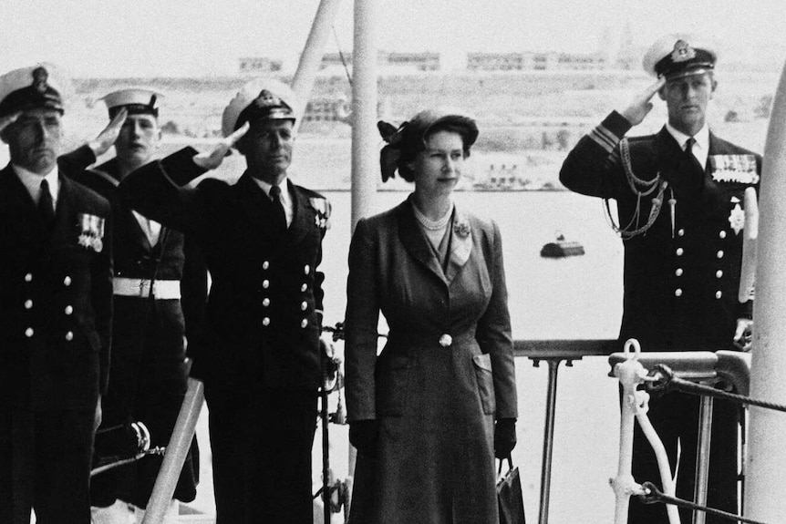 A black and white photograph of Princess Elizabeth on a naval ship with Prince Philip saluting in the background.