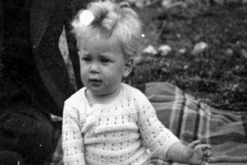 Black and white photo of Adams as a small child sitting on a picnic rug.