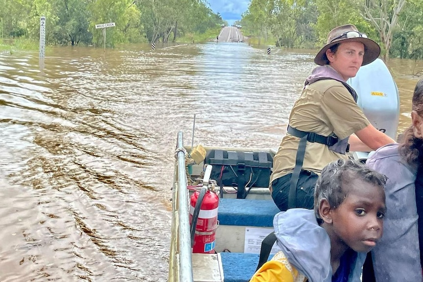 Three people drive atop flood waters on a road in Katherine.
