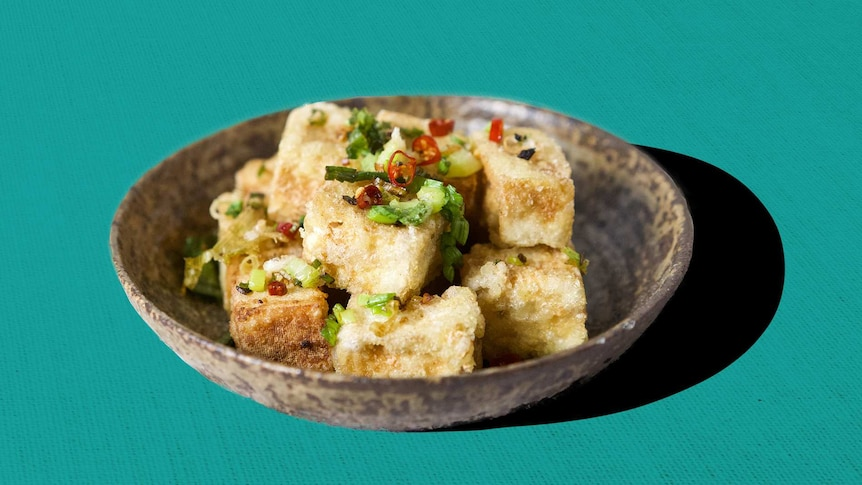 A bowl with salt and pepper tofu, garnished with chilli and shallots in a story about how to cook tofu properly.