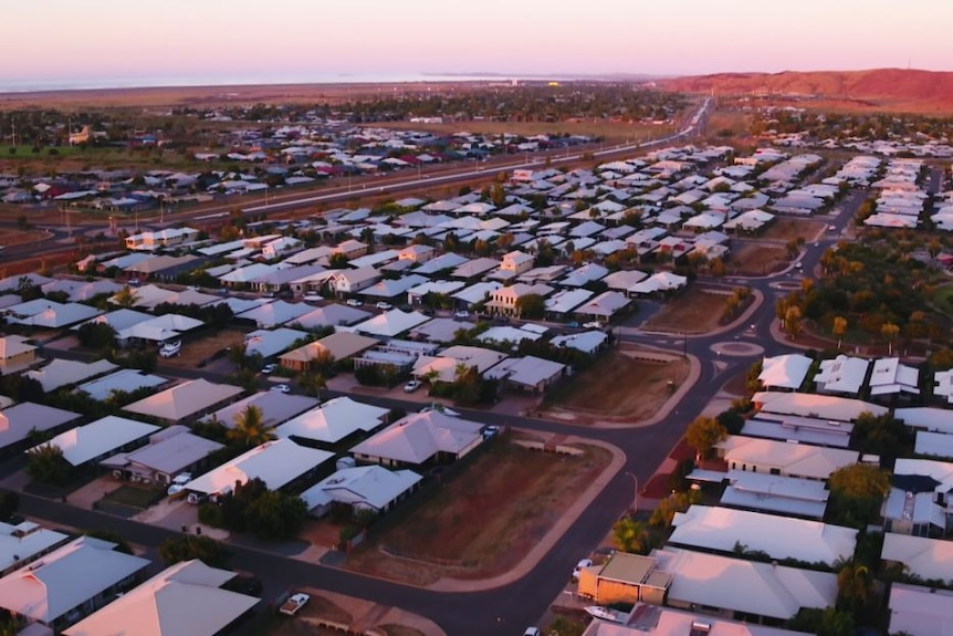An aerial photo shows hundreds of houses in Karratha with white roofs on red dirt.