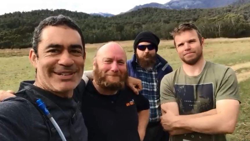 A group of four paramotor pilots standing arm-in-arm following a 1600km journey.