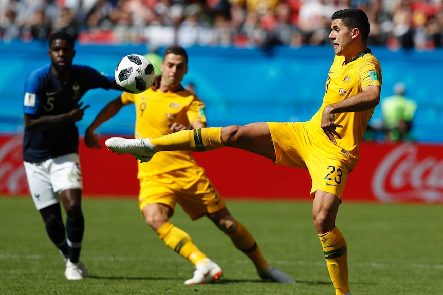 Tom Rogic stretches for the ball