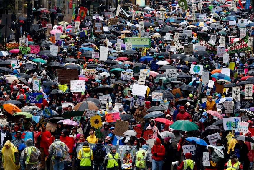 Demonstrators in Chicago march against Mr Trump's climate policies and his actions during his first 100 days in office.