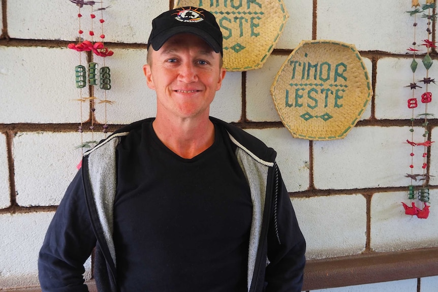 A man is smiling in front a brick wall he is wearing a black hat, shirt and jacket