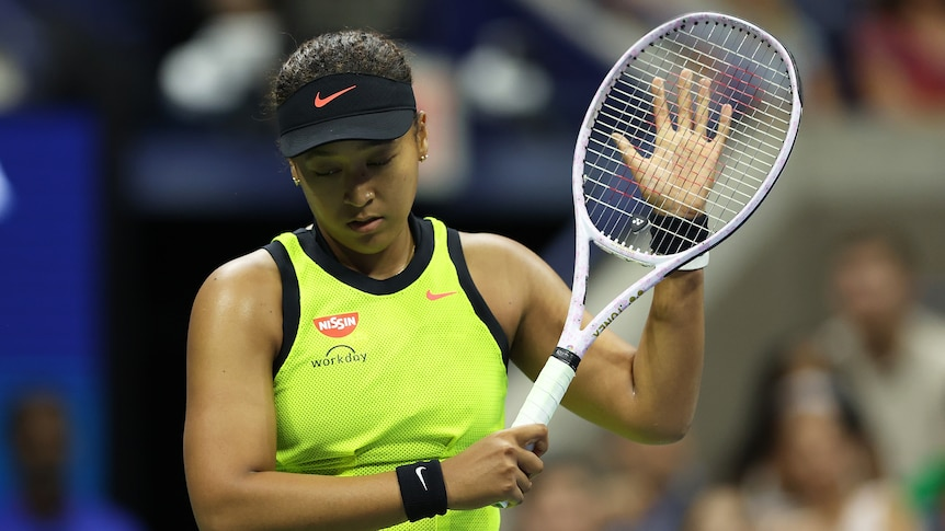 Women with her tennis racket looking disappointed during a match