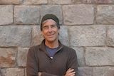A man in a brown beanie and jumper standing in front of a brick wall