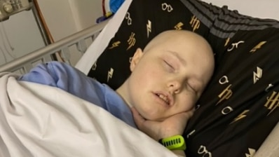 A teenage cancer patient sleeps in a bed.