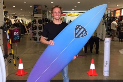 Surfer Tim Dickson posing for a photograph with his surfboard