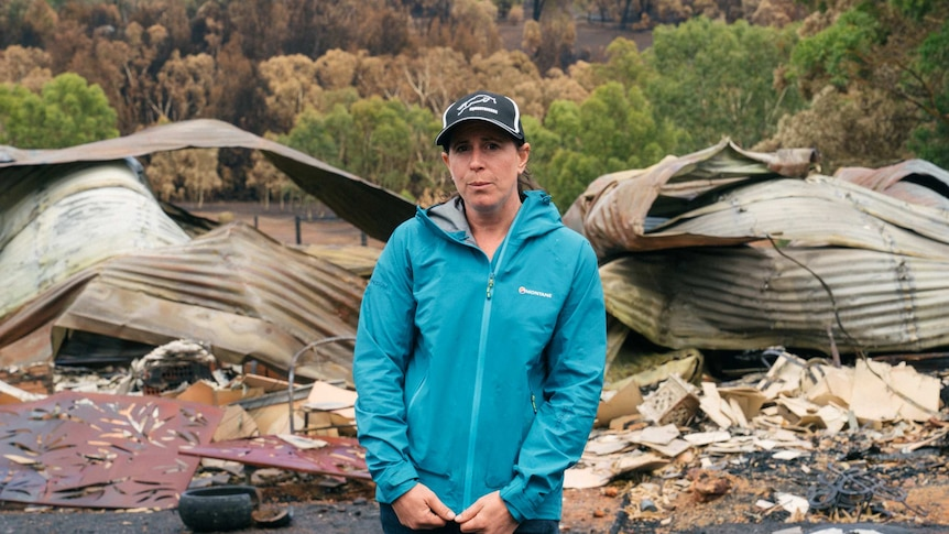 A woman in a blue tracksuit stands outside her burnt down home