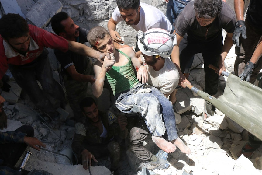 Syrian civil defence volunteers, known as the White Helmets, carry a young boy rescued in Aleppo.