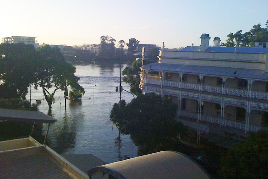 Sun rises over floodwaters lapping at the Regatta Hotel on Coronation Drive at Toowong in Brisbane on January 13, 2011.
