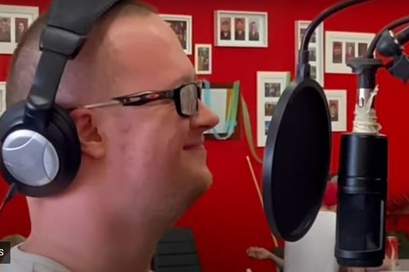 A man wearing glasses stands at a microphone while wearing headphones