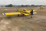A man in a RFS uniform waves at a small yellow aeroplane which sits on a dusty airstrip in bushfire smoke.