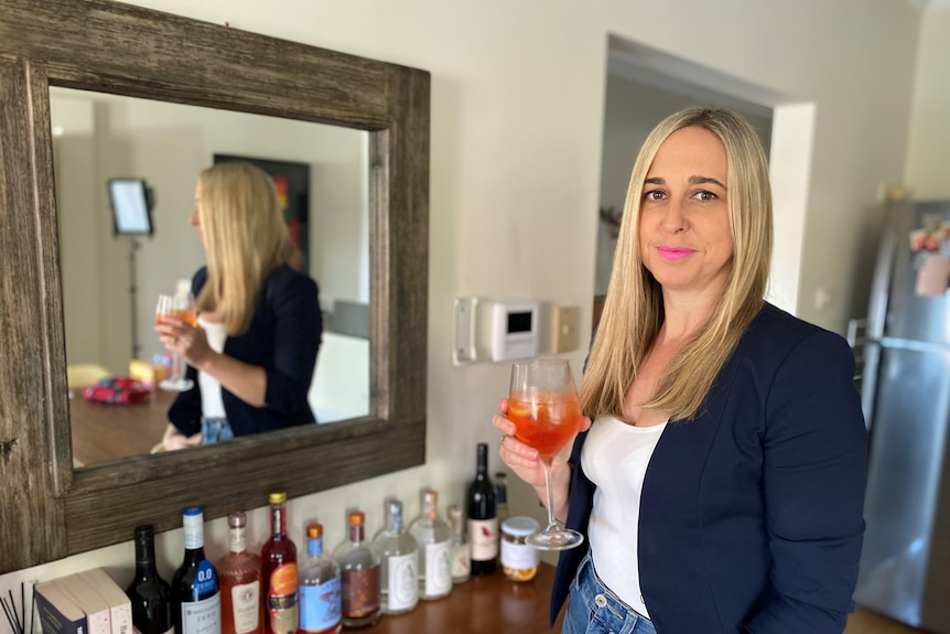 A woman standing in front of a mirror holding a non-alcoholic drink.