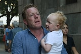 A man carrying a young child flees the scene of a car attack.