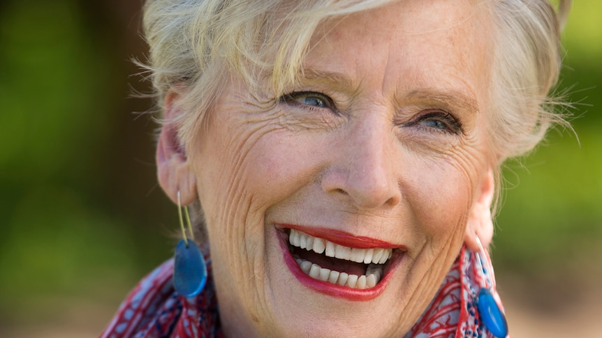 Maggie Beer has a big smile. She has grey hair, cut short, and is wearing bright red lipstick and a scarf to match.