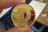 A photo of a gold 'Dogecoin' between two fingers