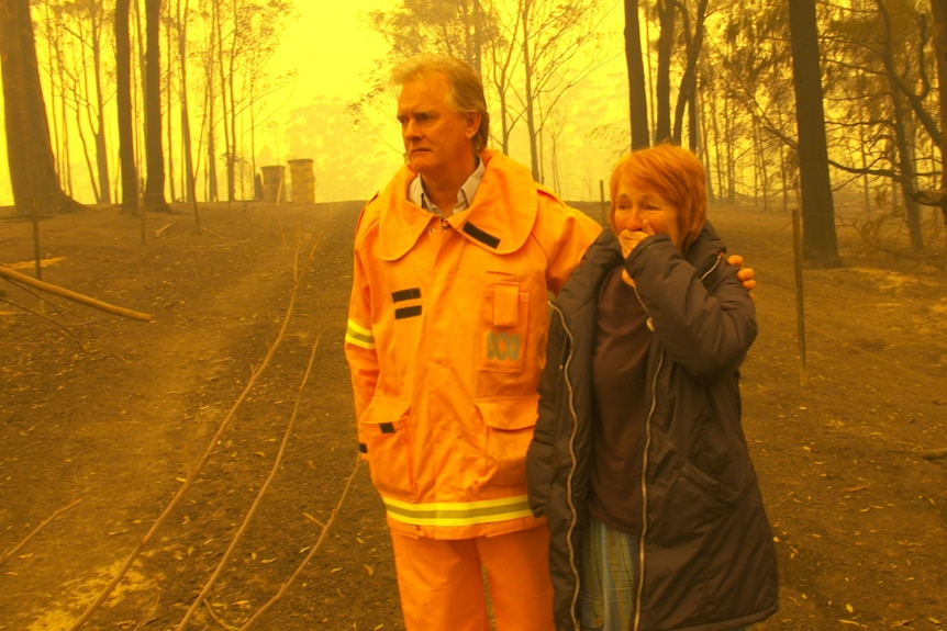 Williams in yellow protective fire suit with arm around woman with hand over her mouth in shock, amid burnt bush and yellow sky.