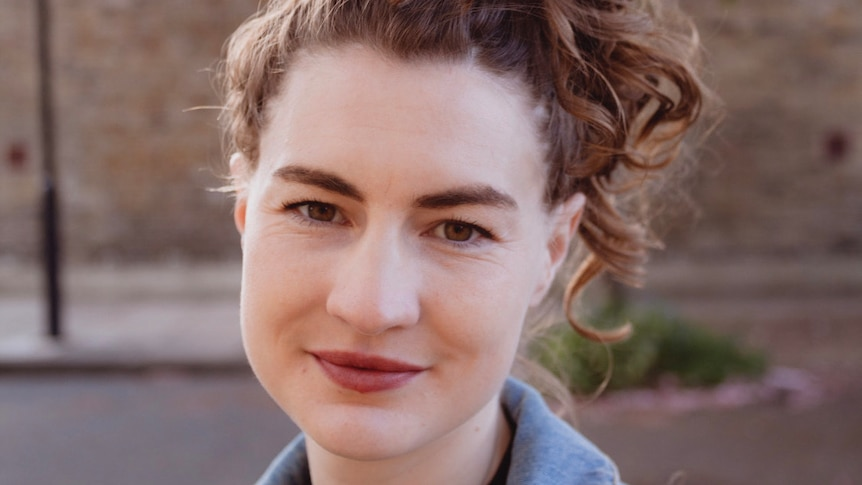 A close up photo of Lucia Osborne-Crowley, a woman with brown curly hair wearing brown lipstick and a blue shirt