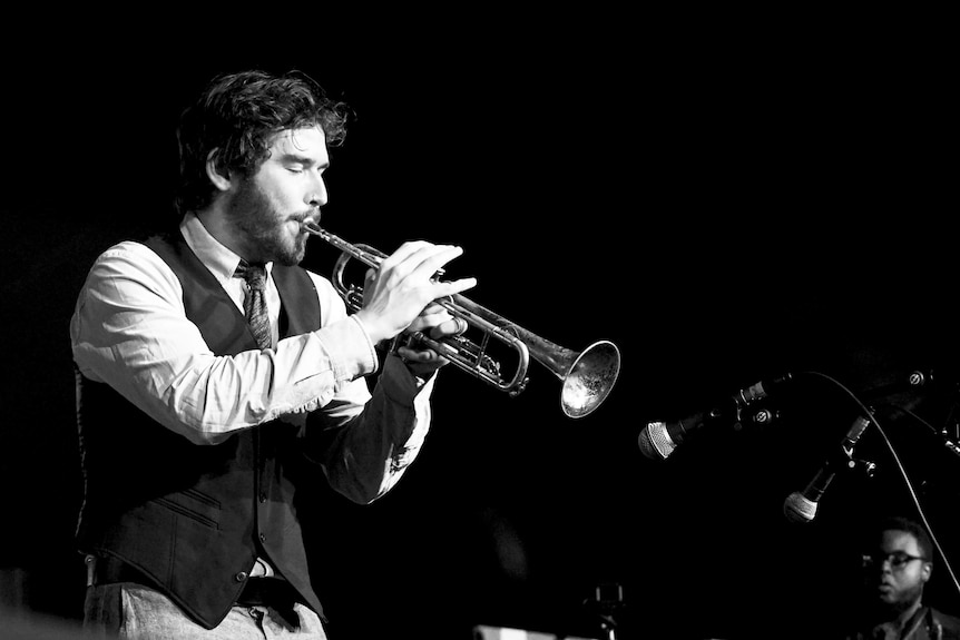 A black and white photo of a man playing a trumpet