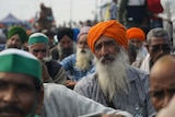 a man wearing orange headwear sits among a crowd of seated protesting farmers