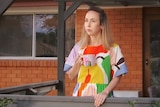 A lady in a colourful dress stands on her porch with a coffee mug staring into the middle distance