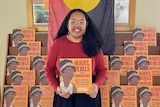 A woman with long dark hair holding an orange book with an aboriginal flag draped in background