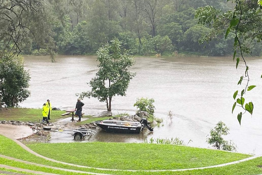 Police and authorities near a wildlife management boat at Lake Placid on a rainy day near Cairns in Far North Queensland.