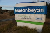 A sign that says Queanbeyan with words 'country living city benefits' written on it