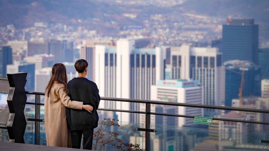 A Korean woman puts her arm around a man as they look across a railing at the Seoul skyline