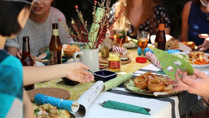 La gente se reúne alrededor de la mesa para el almuerzo de Navidad.