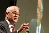 Malcolm Turnbull gestures as he speaks at a podium with a televised image of him on a large screen behind.