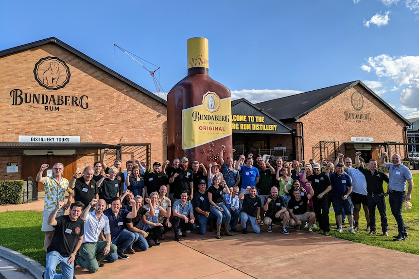 A large number of people pose for a photo outside the Bundaberg Rum distillery on a sunny day.