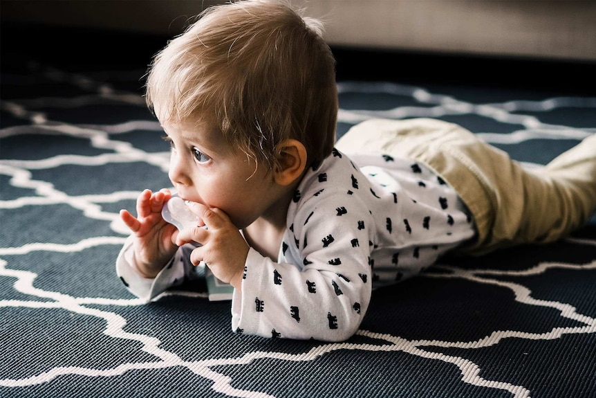 Cute crawling baby sucking on a dummy for a story about why parents are choosing masculine names for their girls.