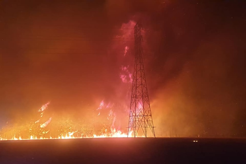 A powerline tower is ablaze with huge flames towering behind it, in a field.