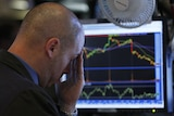 A trader reacts to the monitor shortly before the closing bell as he works on the floor of the New York Stock Exchange