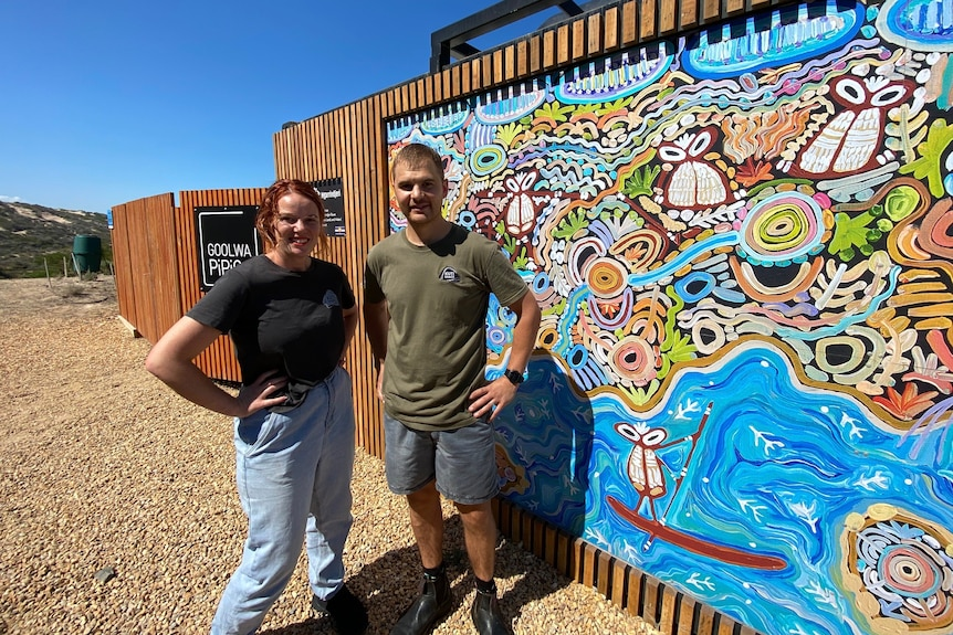A woman and a man stand in front of a cafe with a mural on a wall