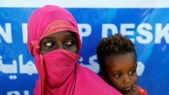 A woman wearing a pink headscarf carries her child