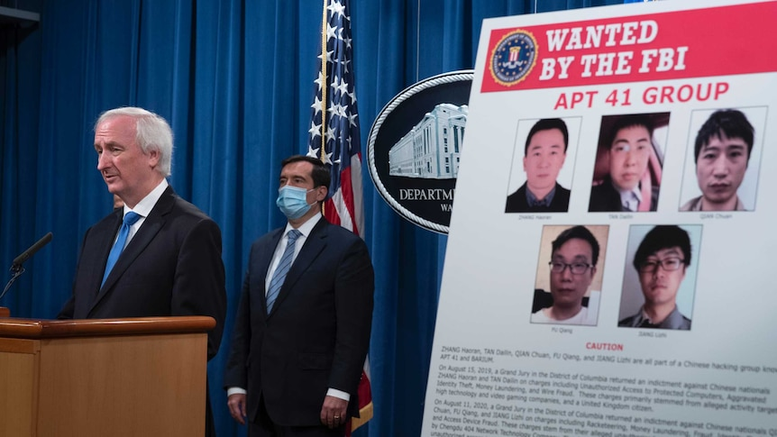 Deputy Attorney General Jeffrey Rosen speaks from a podium next to a poster with five faces of the Chinese hackers.