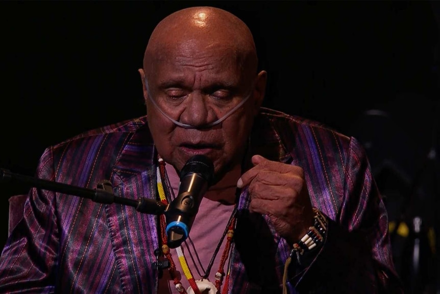 Archie Roach sings into a microphone