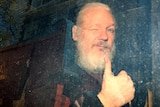 WikiLeaks founder Julian Assange is seen through a dirty police van window as he winks and throws a thumb in the air.