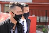Two men wearing face masks walk along a city street.