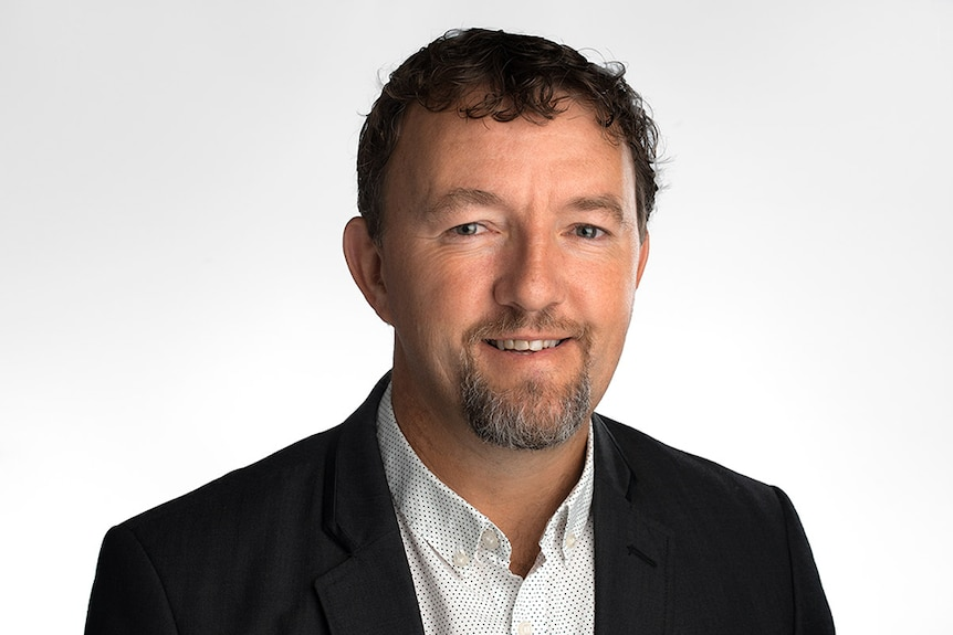 A headshot of a youngish executive, with a beard, smiling.