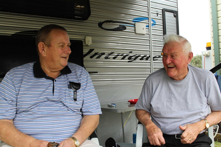Two men sitting in camping chairs laugh, looking at each other, out the front of a caravan