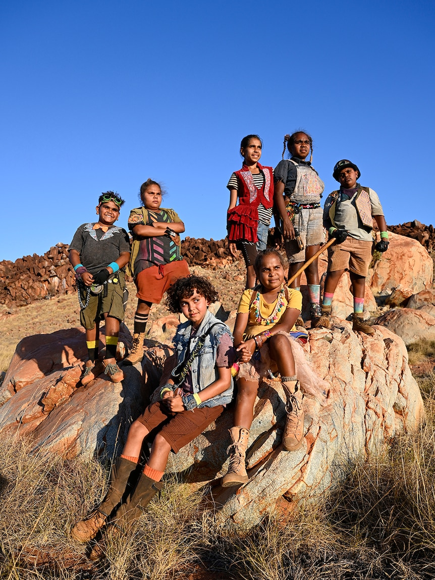 Six tweens stand and sit on large rocks looking into the distance in rocky spinifex desert landscape on sunny clear blue sky day