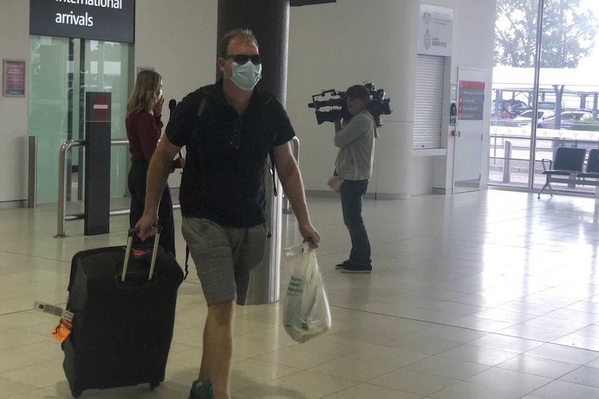 A man walks through an airport holding a suitcase and a bag and wearing a face mask.