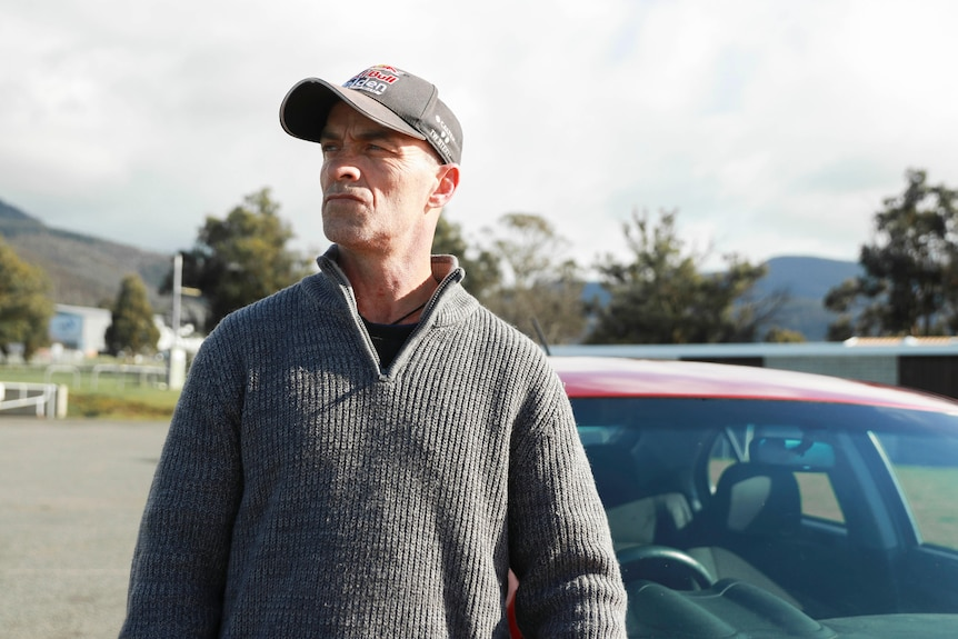 Jason Browne, wearing a cap, standing on the street in front of his car.